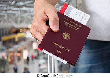Person With Luggage Holding Passport And Boarding Pass...