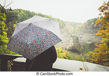 Person with umbrella looking at mountain landscape