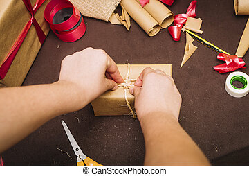 Person wrapping christmas gifts with brown paper and red ribbon.