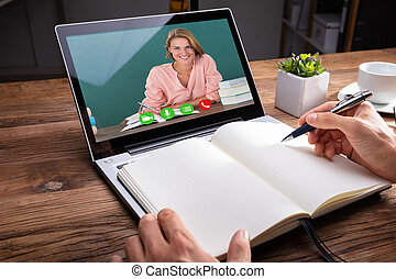 Person Writing On Notebook While Video Chatting