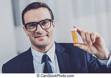 Personable man showing a pill box