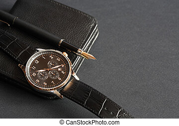 Wristwatch and fountain pen lying on change purse. Closeup on dark surface
