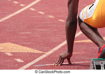 A sprinter in a track and field race is poised at the starting line waiting for the start
