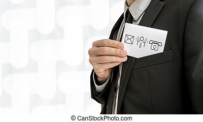 Personal business consultant  removing a business card with communication icons from the inner pocket of his jacket
