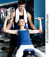 Personal coach helps woman to exercise with weights