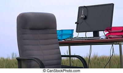Personal computer on a desk in green field