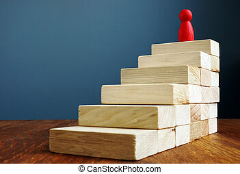 Personal development and growth, success in career concepts. Stairs and red figurine as symbol of leader.