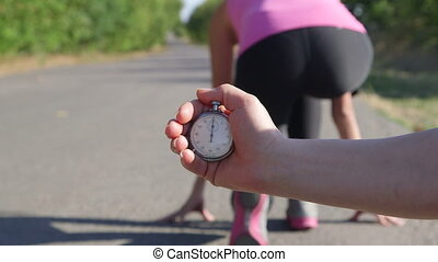 Personal fitness coach with stopwatch in hand timing female runner on road