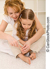 Personal grooming - woman and little girl cutting toe nails