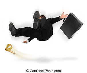 Businessman slipping and falling from a banana peel on a white background