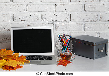 Personal laptop computer on wood table over brick wall background.