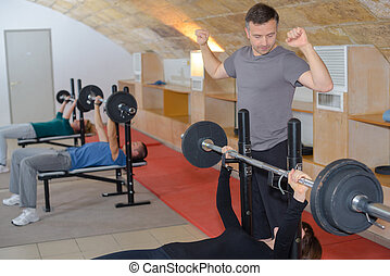 personal male trainer helping young woman with lifting barbell