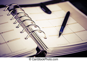 Personal organizer or planner with pen on white background...