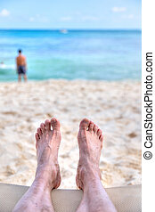 Personal perspective of man relaxing at sandy beach with feet view towards sea view and copy space. Shot taken in the Caribbean coast of Mexico at Cancun.