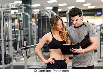 Personal trainer and client looking at her progress at the...