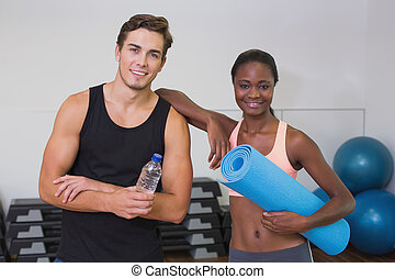 Personal trainer and client smiling at camera at the gym