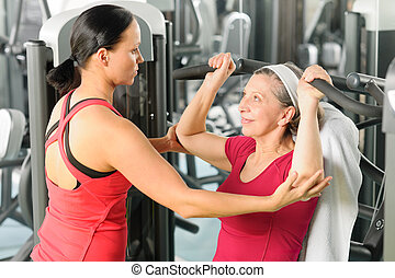 Personal trainer assist senior woman at gym - Personal ...