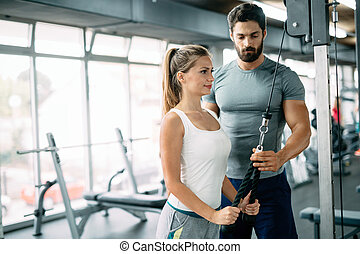 Personal trainer assisting beautiful woman lose weight
