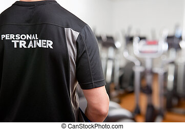 Personal Trainer, with his back facing the camera, looking at a gym