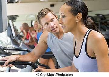 Personal Trainer Encouraging Woman Using Treadmill At Gym