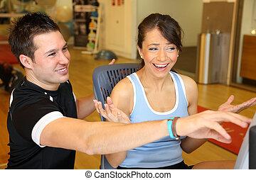 Personal Trainer explaining training bike to female customer