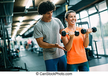 Personal trainer giving instructions in modern gym