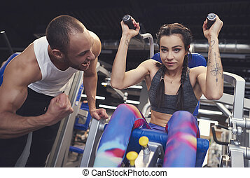 Personal trainer guding young woman at gym