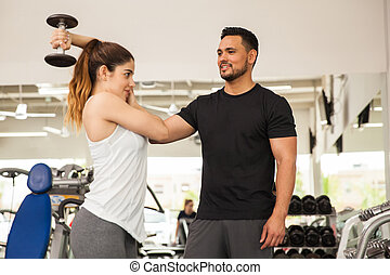 Personal trainer helping a woman at the gym