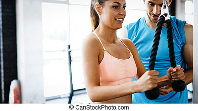 Personal trainer helping beautiful woman in gym