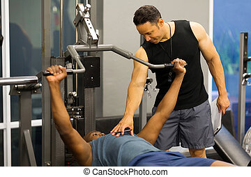 personal trainer helping client lift weights at the gym