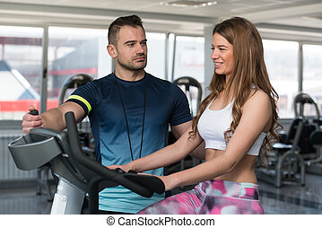 Personal Trainer Helping Client On Bicycle