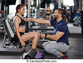 Personal trainer helping woman in the gym
