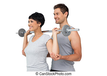 Personal trainer helping woman with weight lifting bar