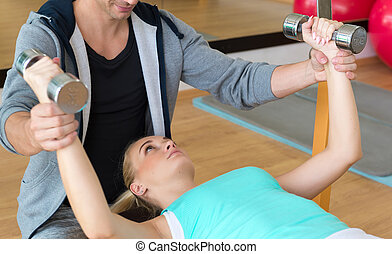 Personal trainer helping woman working with dumbbells