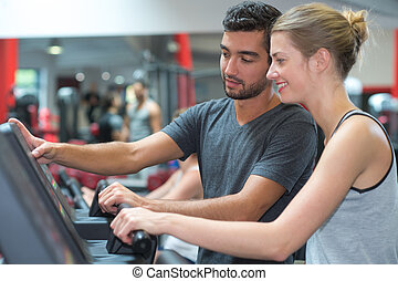 personal trainer helping woman working with treadmill