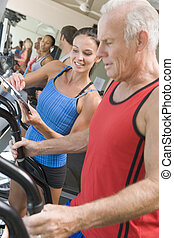 Personal Trainer Instructing Man On Treadmill