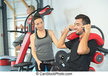 personal trainer instructing trainee in gym