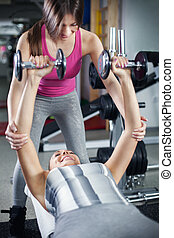 Personal trainer - Cute Sporty young woman doing exercise in...
