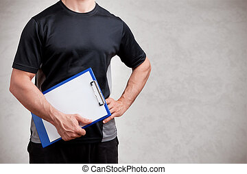 Personal Trainer, with a pad in his hand, isolated in grey