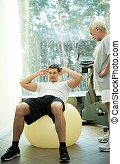 Personal trainer shows to a senior man how to do exercise on a fitness ball