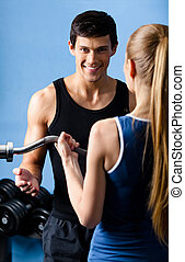Personal trainer shows woman the correct exercise performing