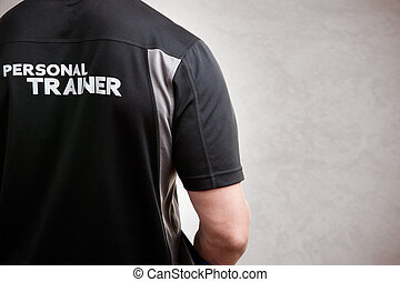 Personal Trainer, with his back facing the camera, in a grey...