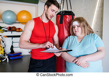 Personal Trainer Talking to Overweight Woman
