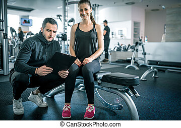Personal trainer talks to his client. - Young male personal...