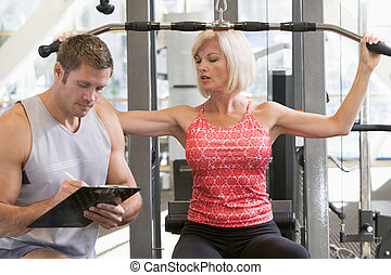 Personal Trainer Watching Woman Weight Train