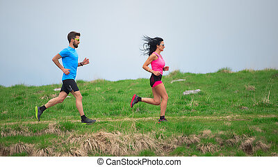 Personal trainer while training his sporty woman to run in the meadows