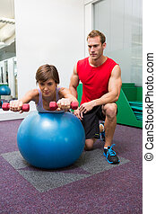 Personal trainer with client lifting dumbbells on exercise ball