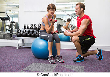 Personal trainer with client sitting on exercise ball lifting du