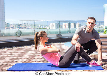 Personal trainer with client who does sit ups.