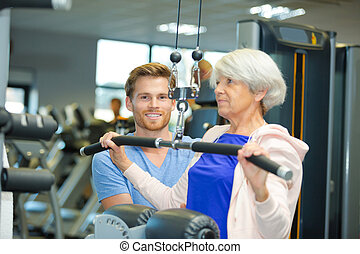 personal trainer with elderly woman in gym
